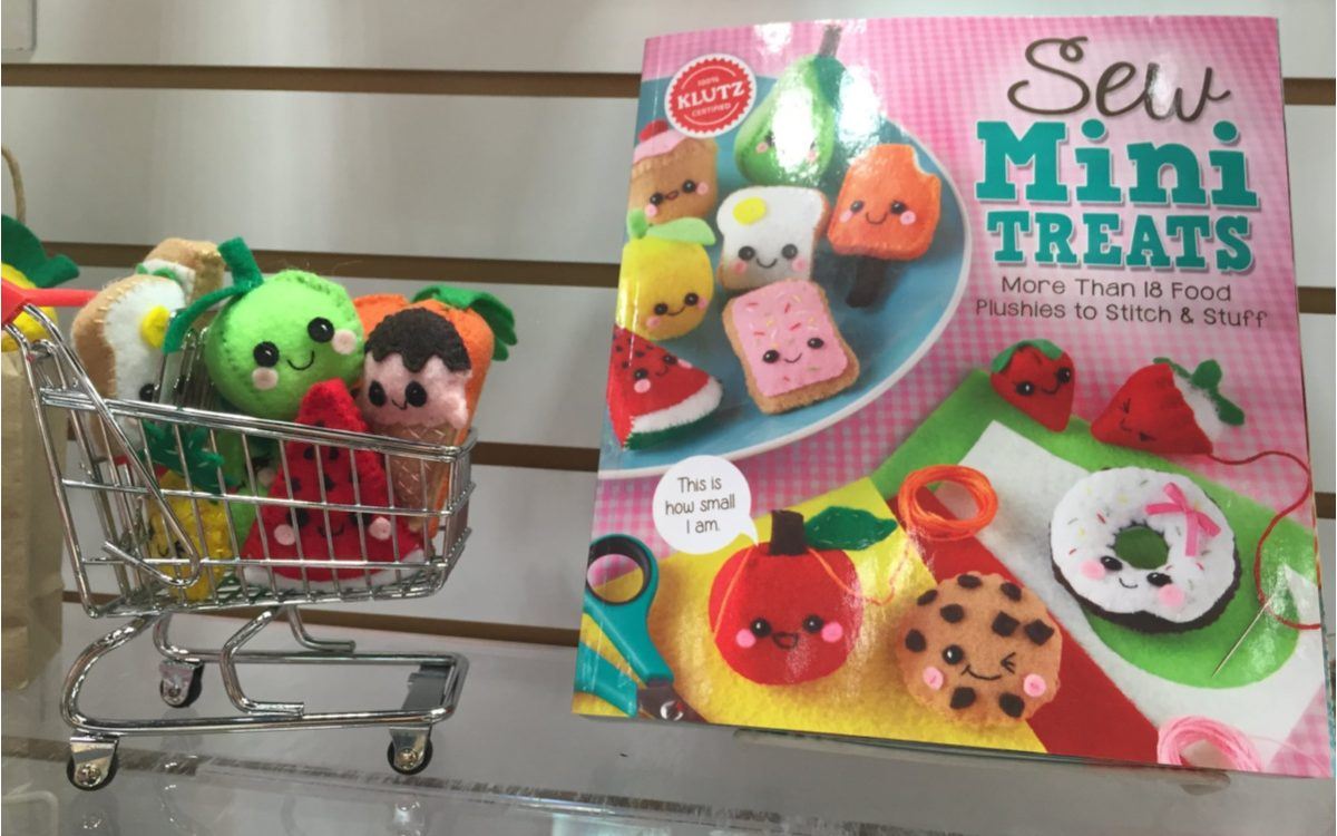mini food plushies in mini shopping cart next to mini plushie sewing kit