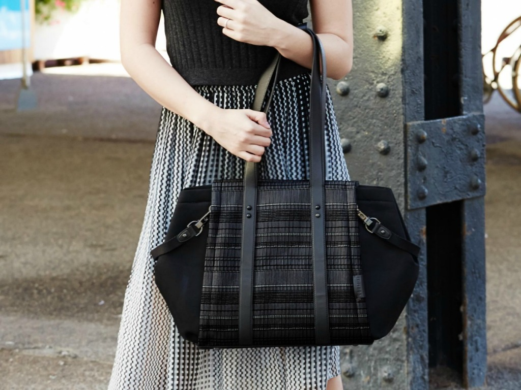 Woman holding a large black fashion diaper bag