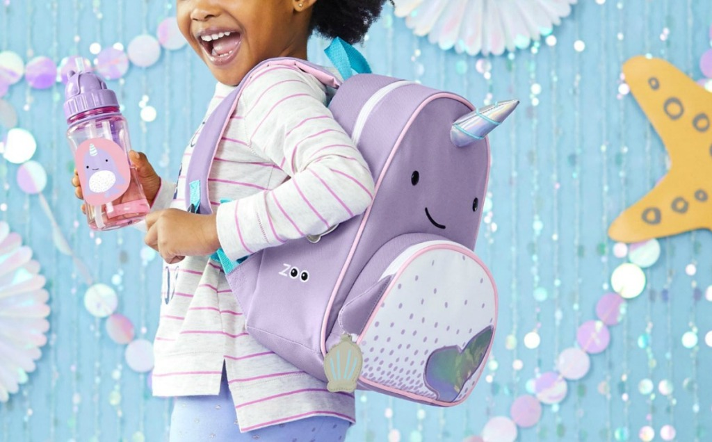 Young girl wearing a narwhal themed backpack