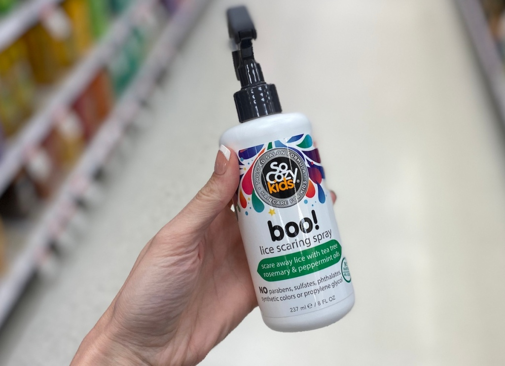 hand holding a bottle of SoCozy kids lice spray