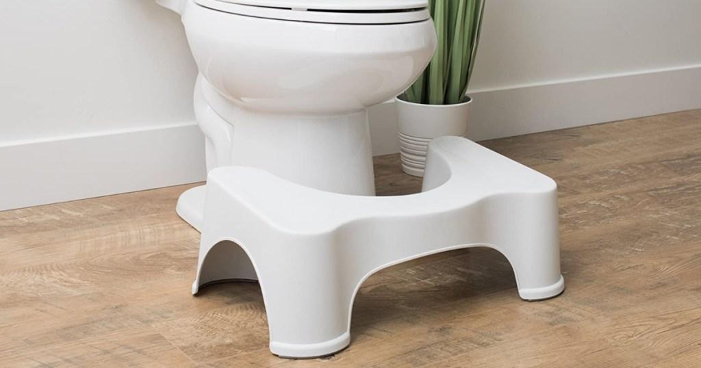 squatty potty in bathroom next to toilet