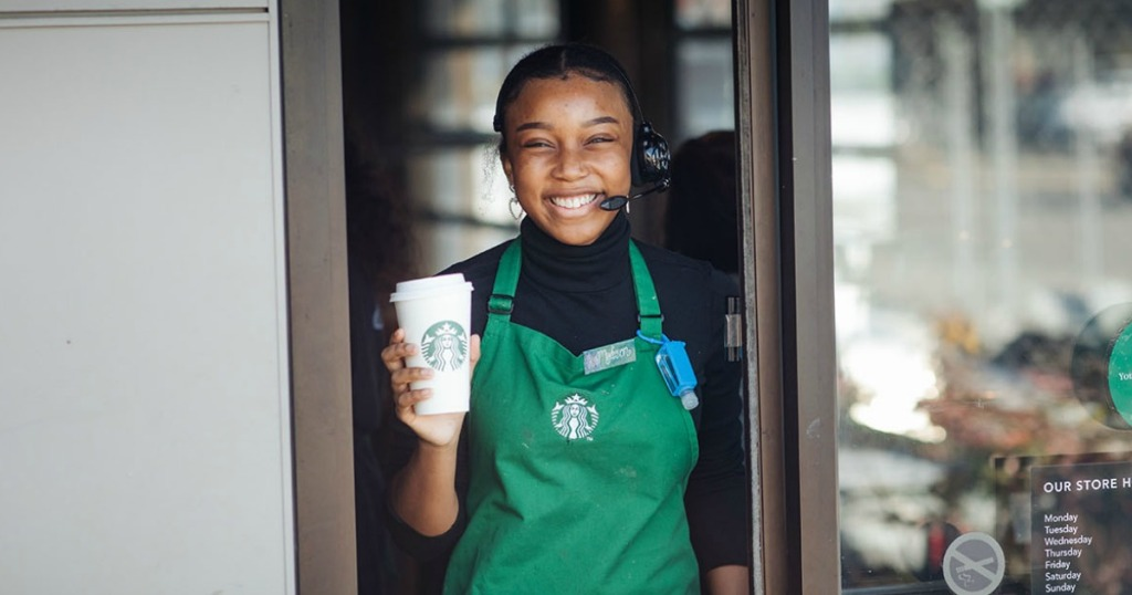 Starbucks barista with Coffee cup in drive-thru