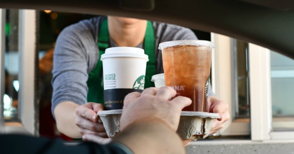 Starbucks employees handing out drinks through the drive through