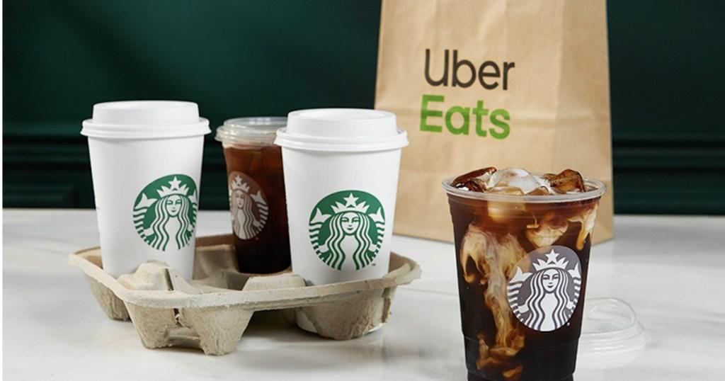 Starbucks drinks next to Uber Eats bag