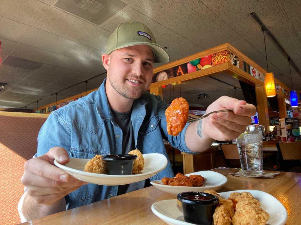 man eating chicken wings at Applebee's