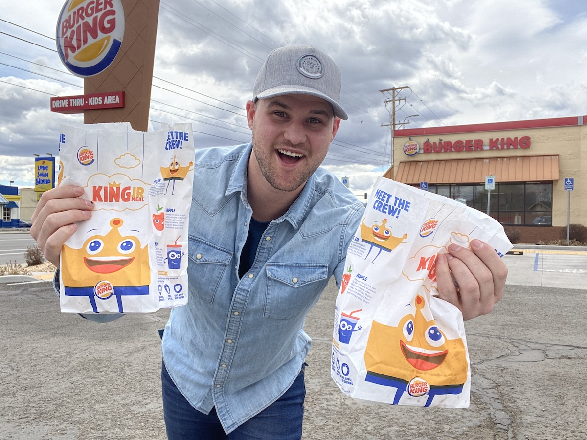 man holding two burger king kids meal bags in front of burger king restaurant
