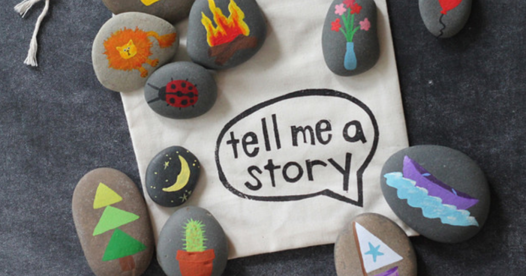 "Story stones with pictures on them next to a sign reading ""tell me a story"""