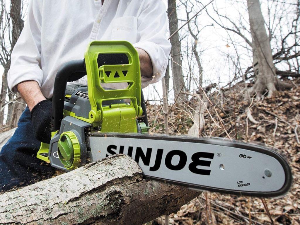man using chain saw to cut tree branch
