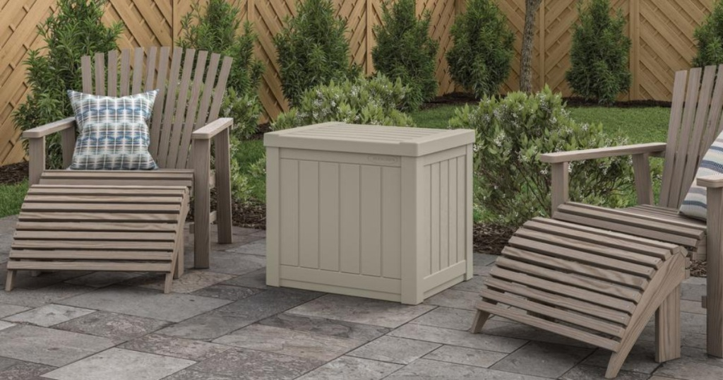 taupe deck box on patio in between lounge chairs