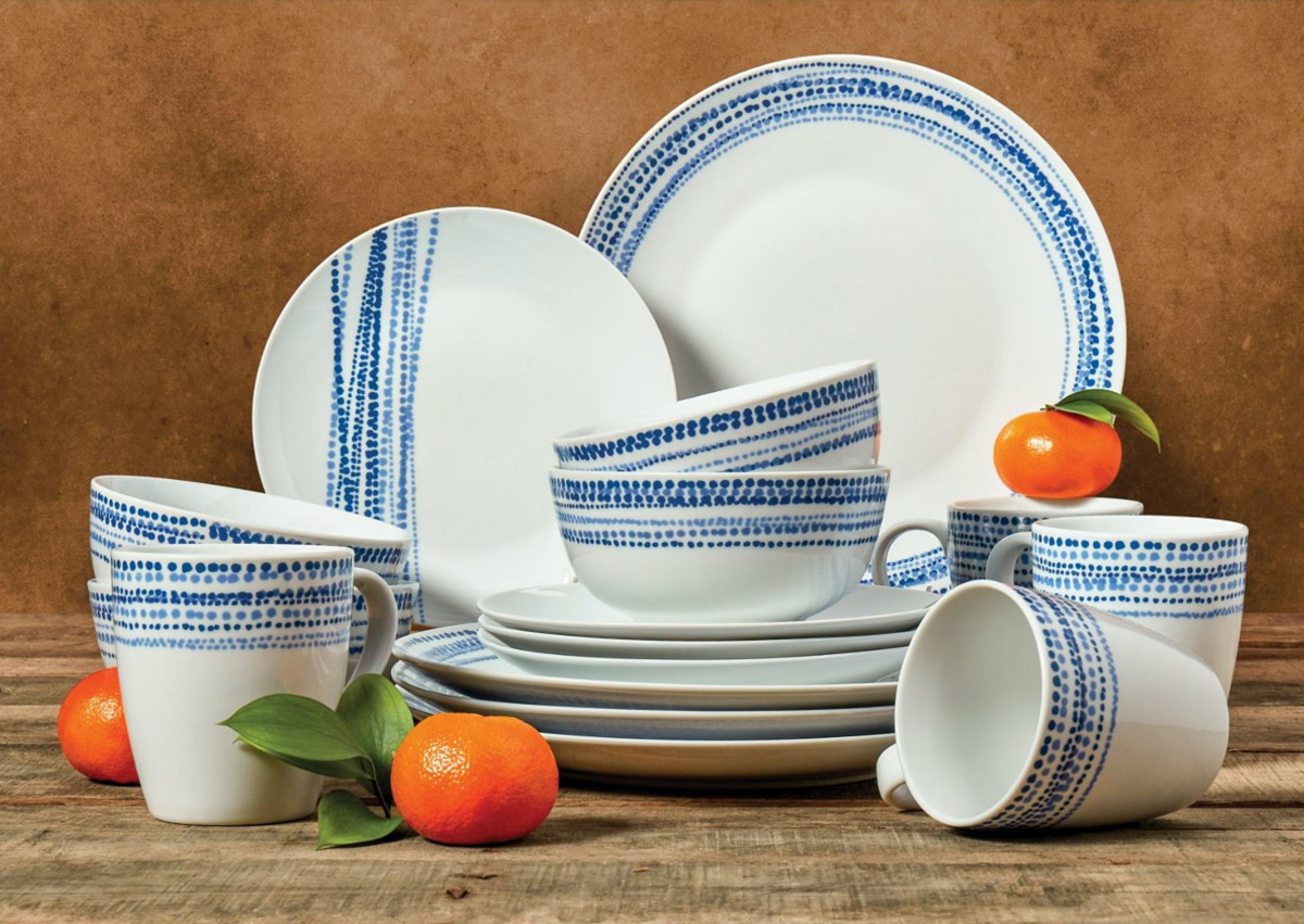 white and blue dinnerware set on counter with small oranges