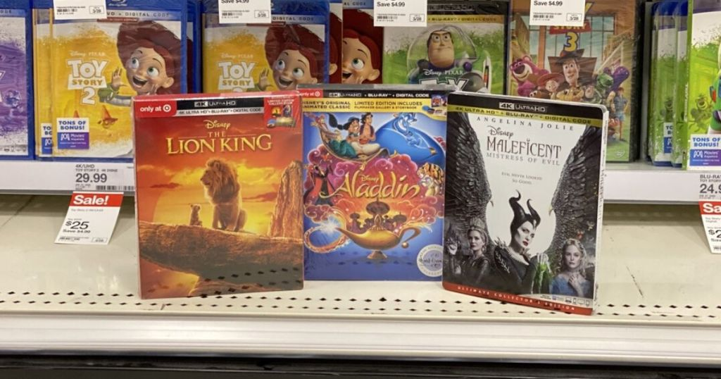 store shelf with three disney 4K movie discs in cases propped up for display