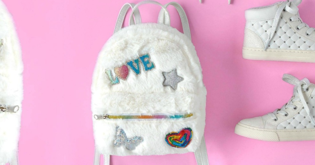 Faux white fur miniature backpack on pink background near matching shoes