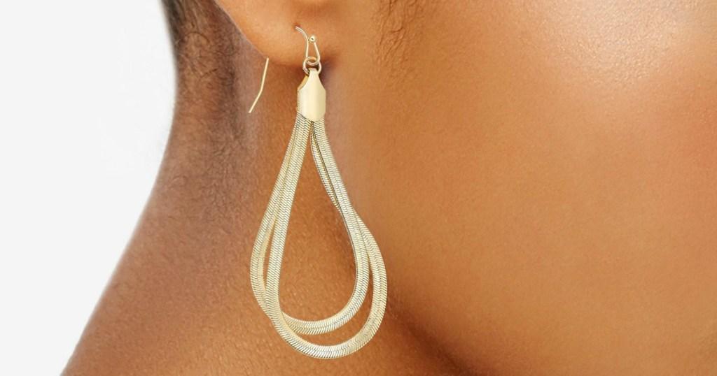 woman wearing gold chain loop earrings