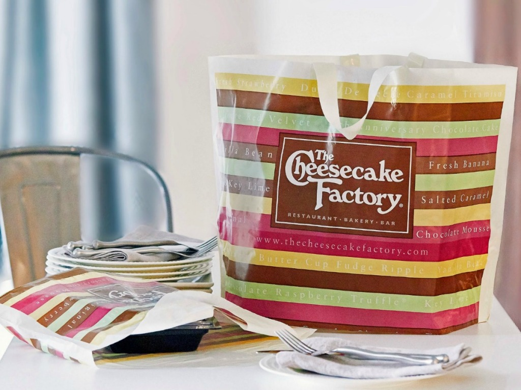The Cheesecake Factory Bags on table next to plates and utensils