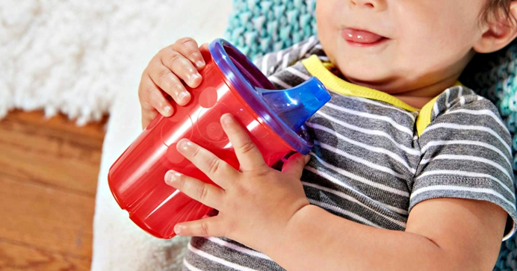 The First Years Take & Toss Spill-Proof Sippy Cup in baby's hands