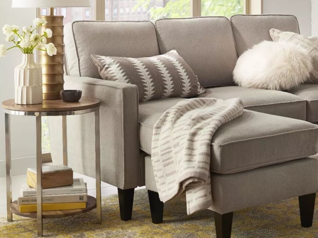 end table with lamp and vase on top and books underneath on lower shelf, next to couch with decorative pillow and throw blanket on it