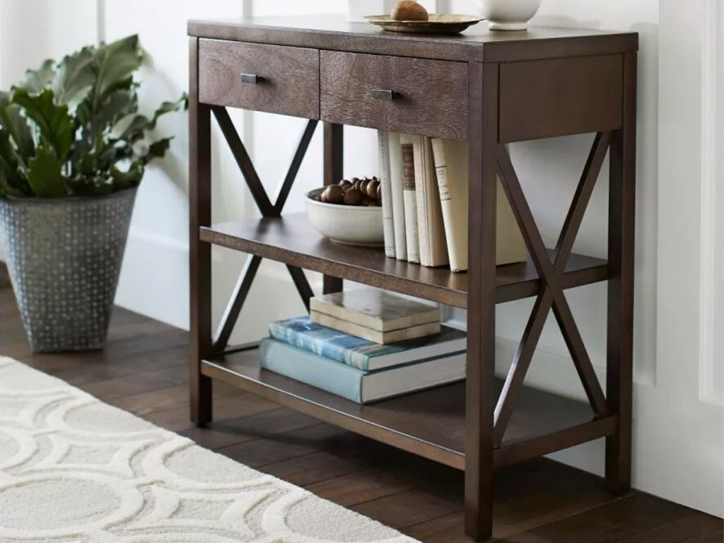 wood console table with two shelves and two drawers with decorative vase on top, bowl and books on middle shelf and books on bottom shelf