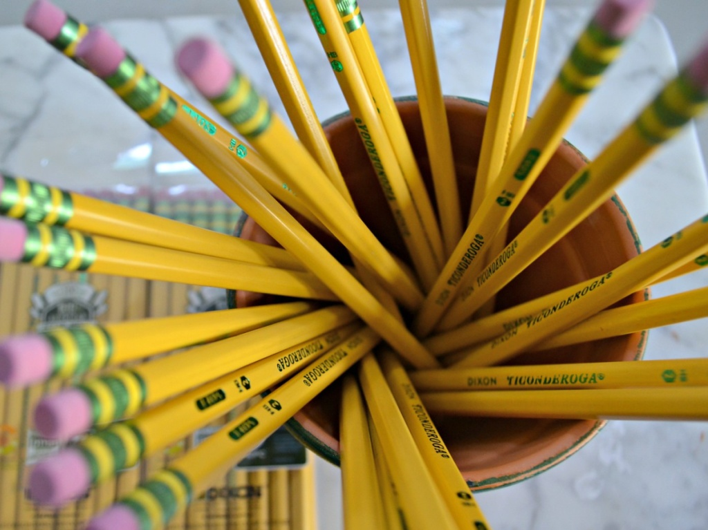 many pencils in cup and package of pencils on table