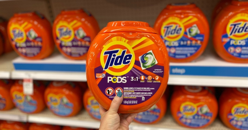 hand holding laundry detergent pods in store aisle