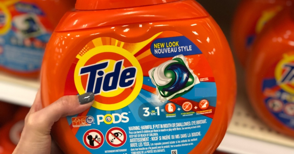 woman's hand holding laundry detergent pac container in store aisle