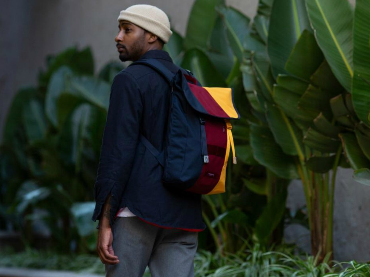 man walking by foilage wearing colorful backpack
