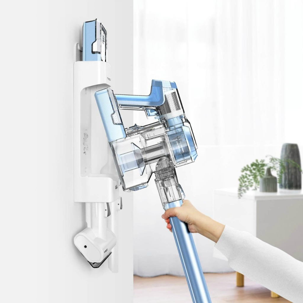 woman putting a cordless vacuum back on a wall charger