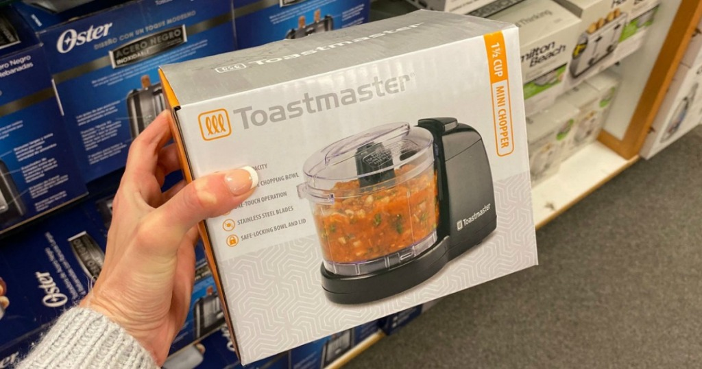 Woman's hand holding a Toastmaster brand toaster in package near in-store display