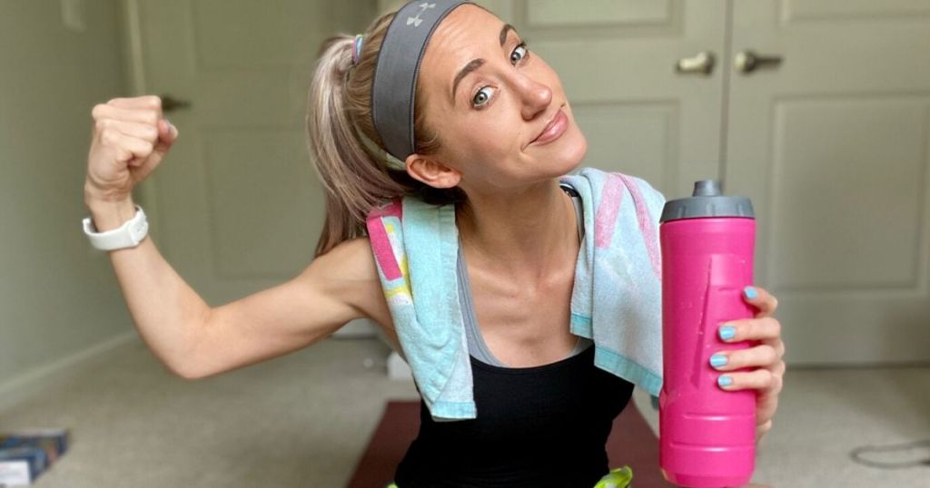 Woman sitting on floor with a water bottle in hand, smiling and flexing arm