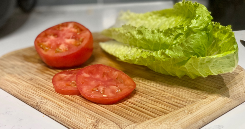 Lettuce and sliced tomatoes on a cutting board with knife