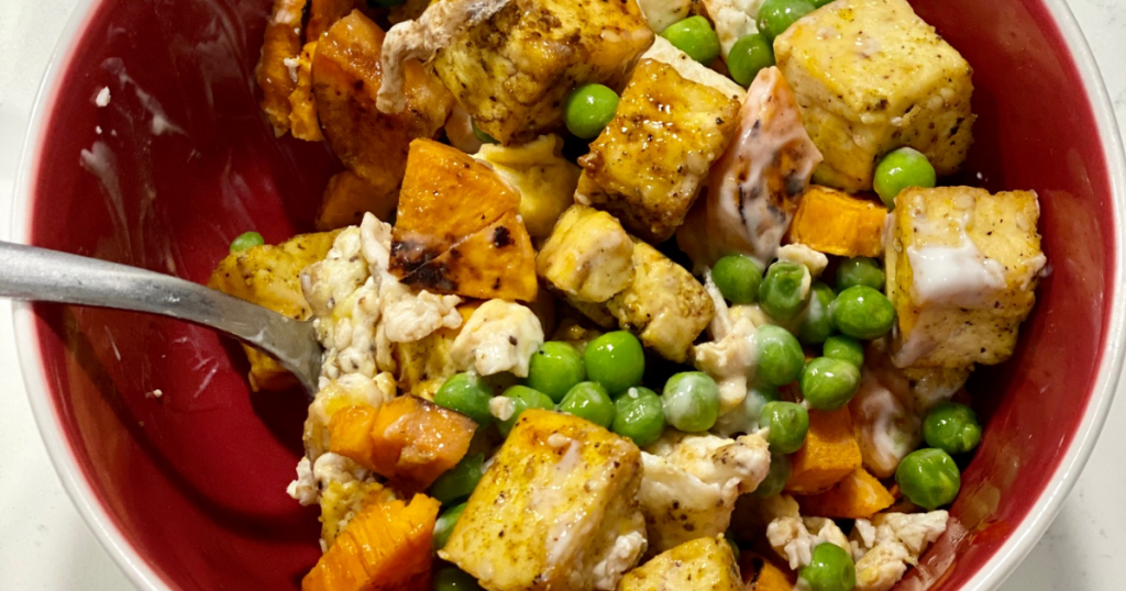 Sweet potatoes, peas, egg whites, and tofu in a bowl on kitchen counter