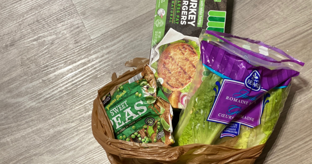 Lettuce, turkey burgers, and peas in a grocery bag in kitchen
