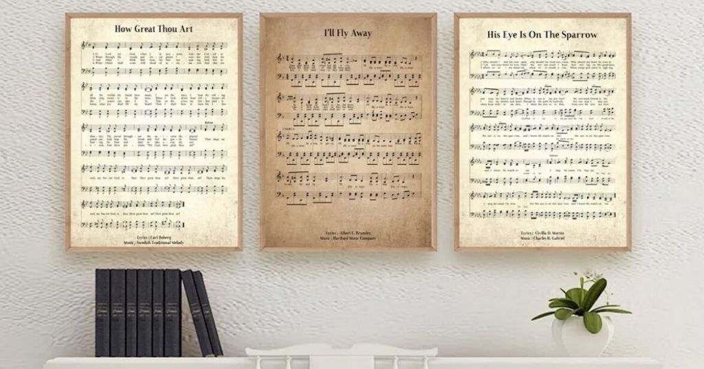three large framed prints hanging over a piano with books on the left side and a plant on the right