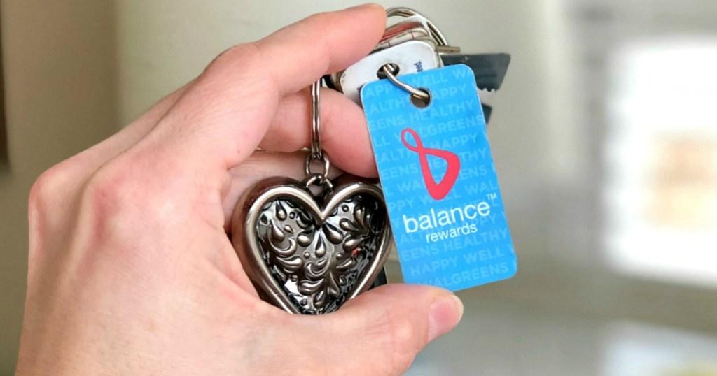 Woman holding Walgreens balance rewards card on keychain