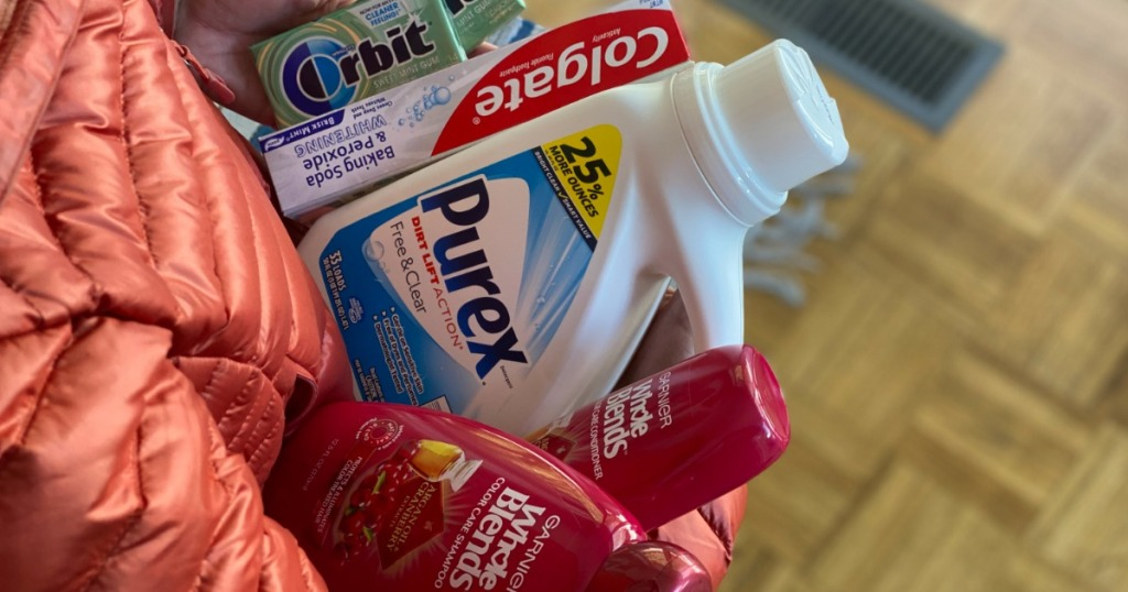 person holding laundry detergent, toothpaste, shampoo and gum