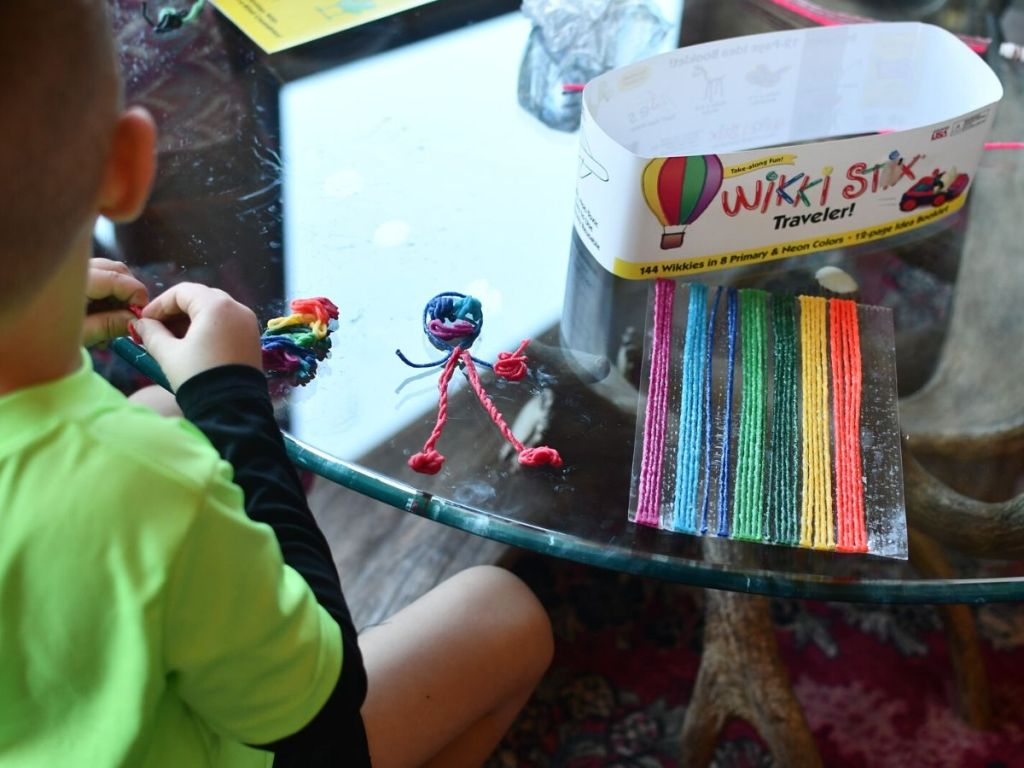 child with back turned playing with moldable wax covered yarn strips on table