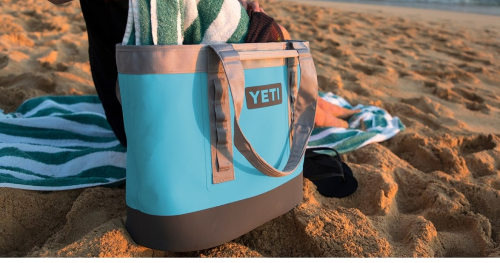 blue YETI bag holding blue and white towel and placed on sand