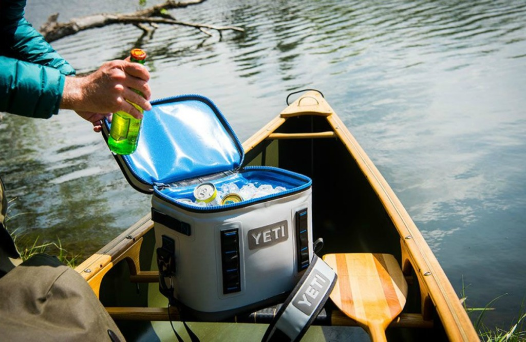 man grabbing water bottle from a YETI cooler on a canoe