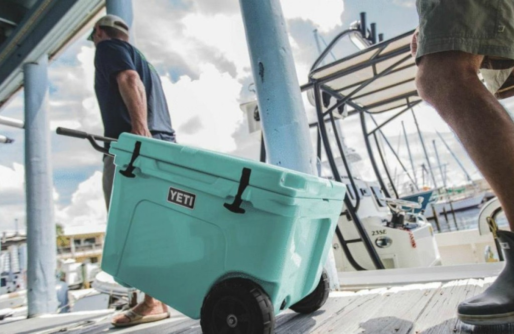 man pulling large teal wheeled cooler