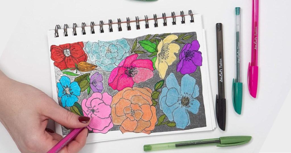 hand holding pink Zebra Pen Doodlerz coloring flowers