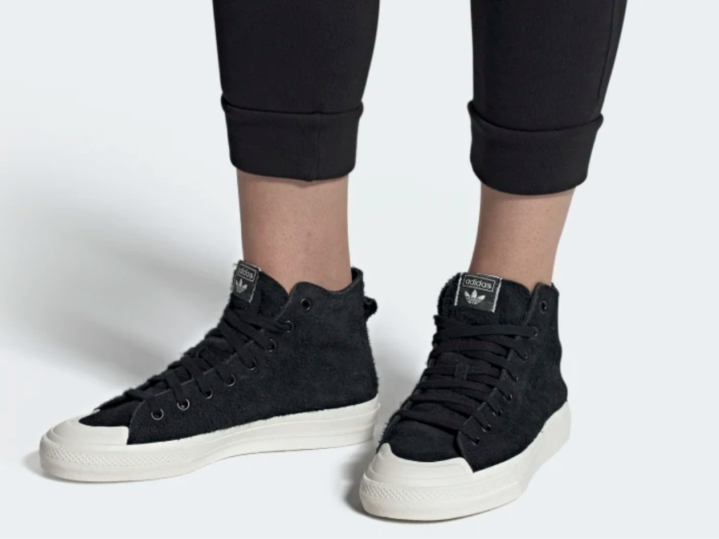 legs wearing black and white adidas shoes