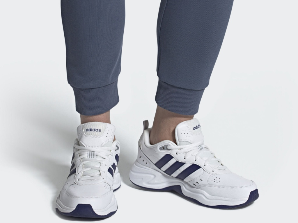 legs wearing white and blue adidas shoes