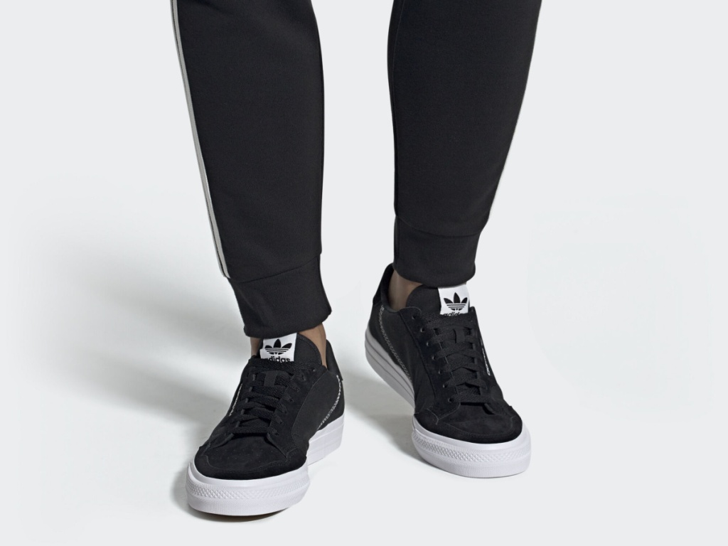 legs wearing black adidas shoes with white soles