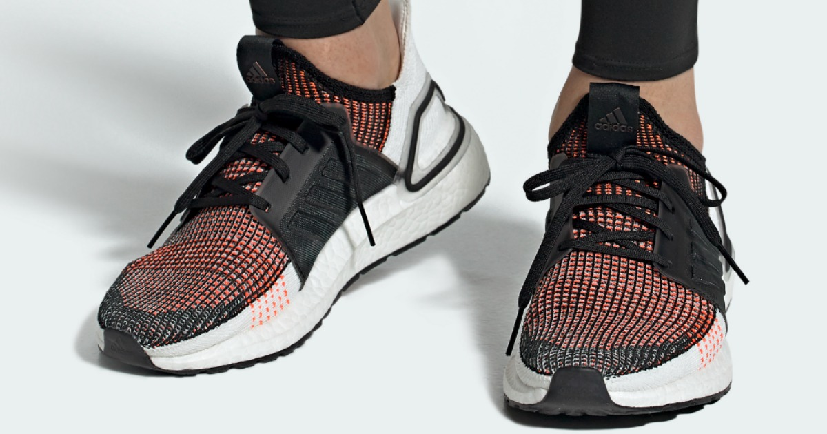 close up of pair of adidas sneakers being worn