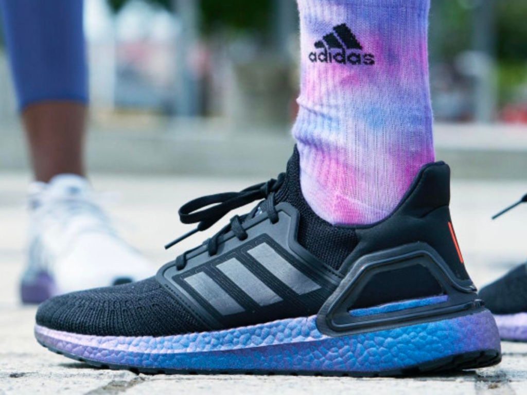 foot wearing black and blue purple Adidas shoes with multi-colored adidas socks