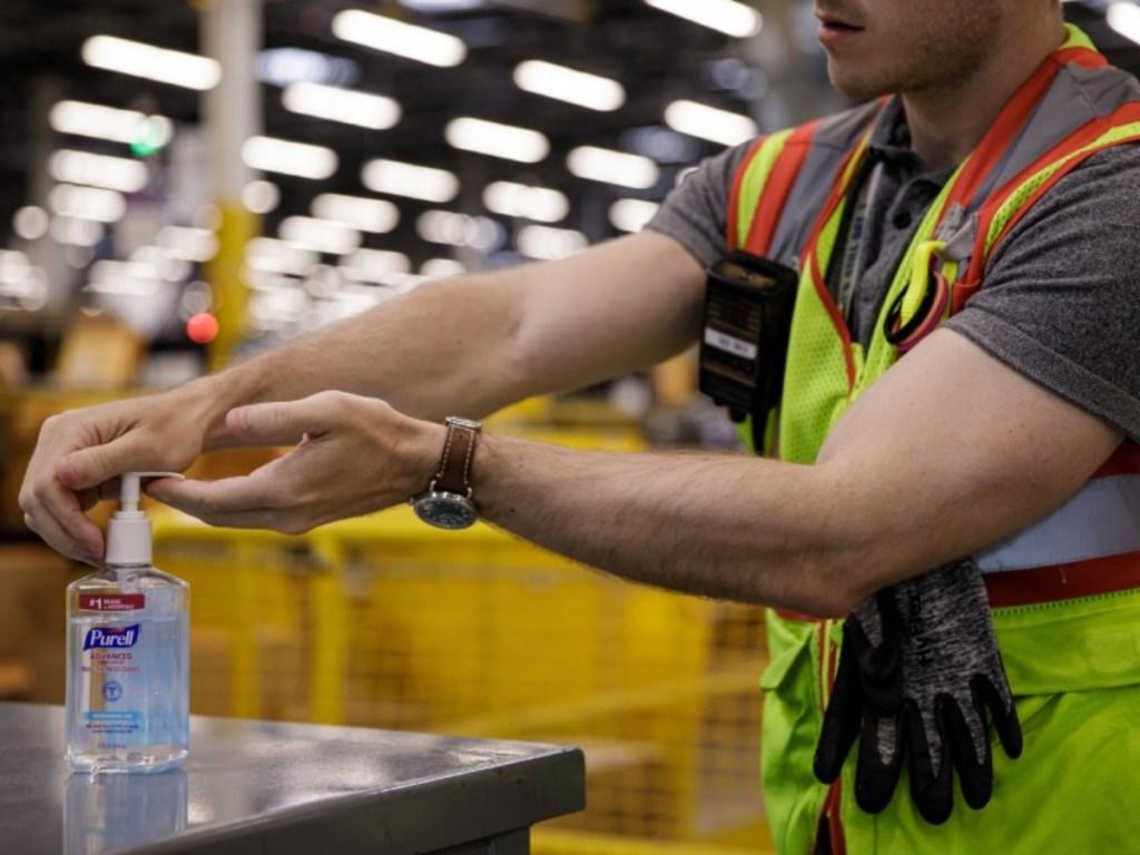 Amazon warehouse employee using hand sanitizer