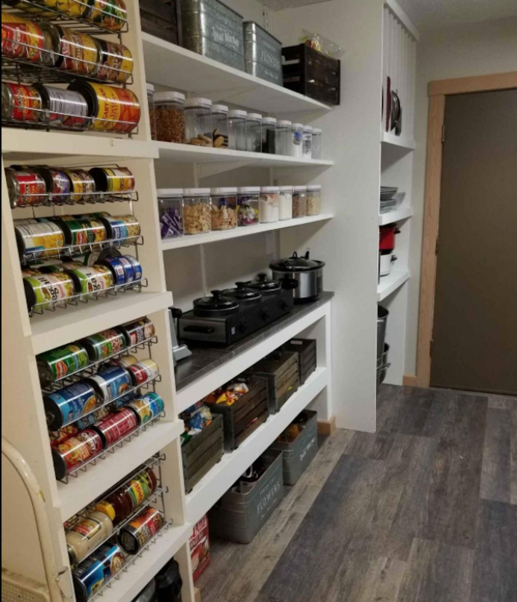 white pantry shelves with various cooking appliances and stacks of can on shelves
