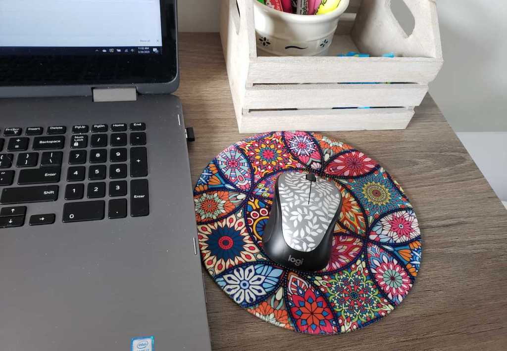laptop next to colorful floral mouse and pad on desk