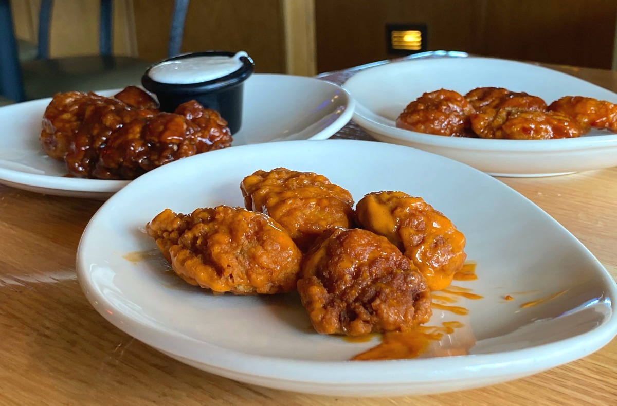 plates filled with boneless wings on a table