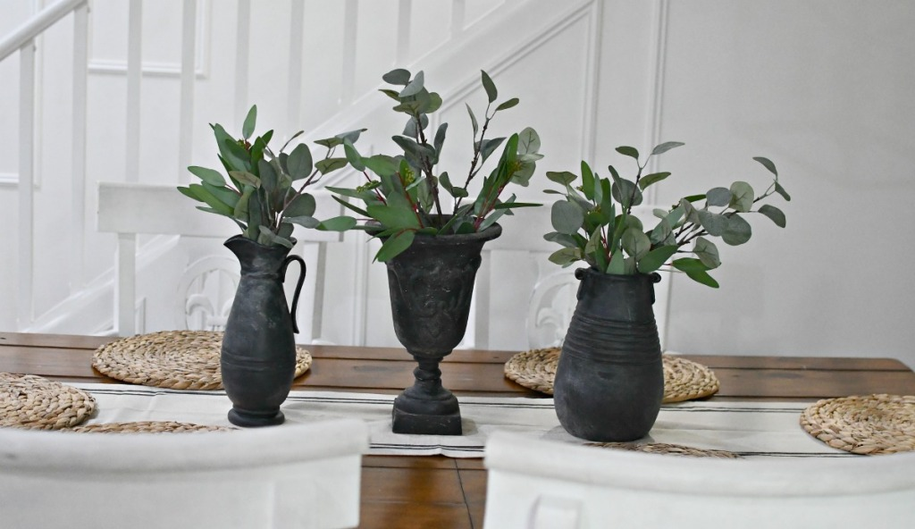 black vases on a table with greenery