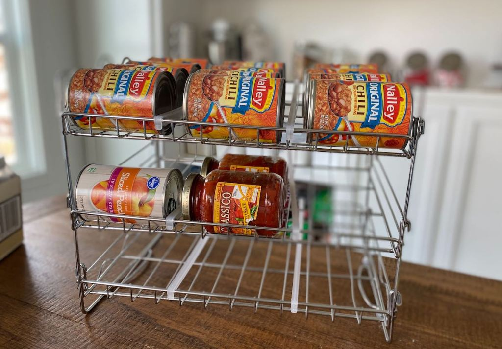 metal can rack on wood table with jars and cans of food